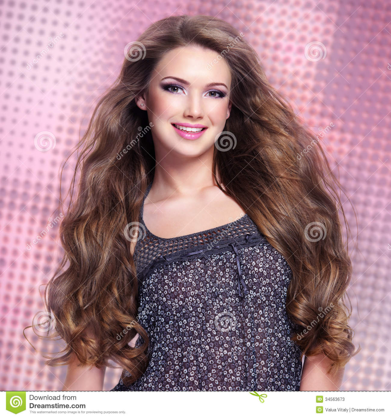 Beautiful young smiling woman with long hairs looking at camera