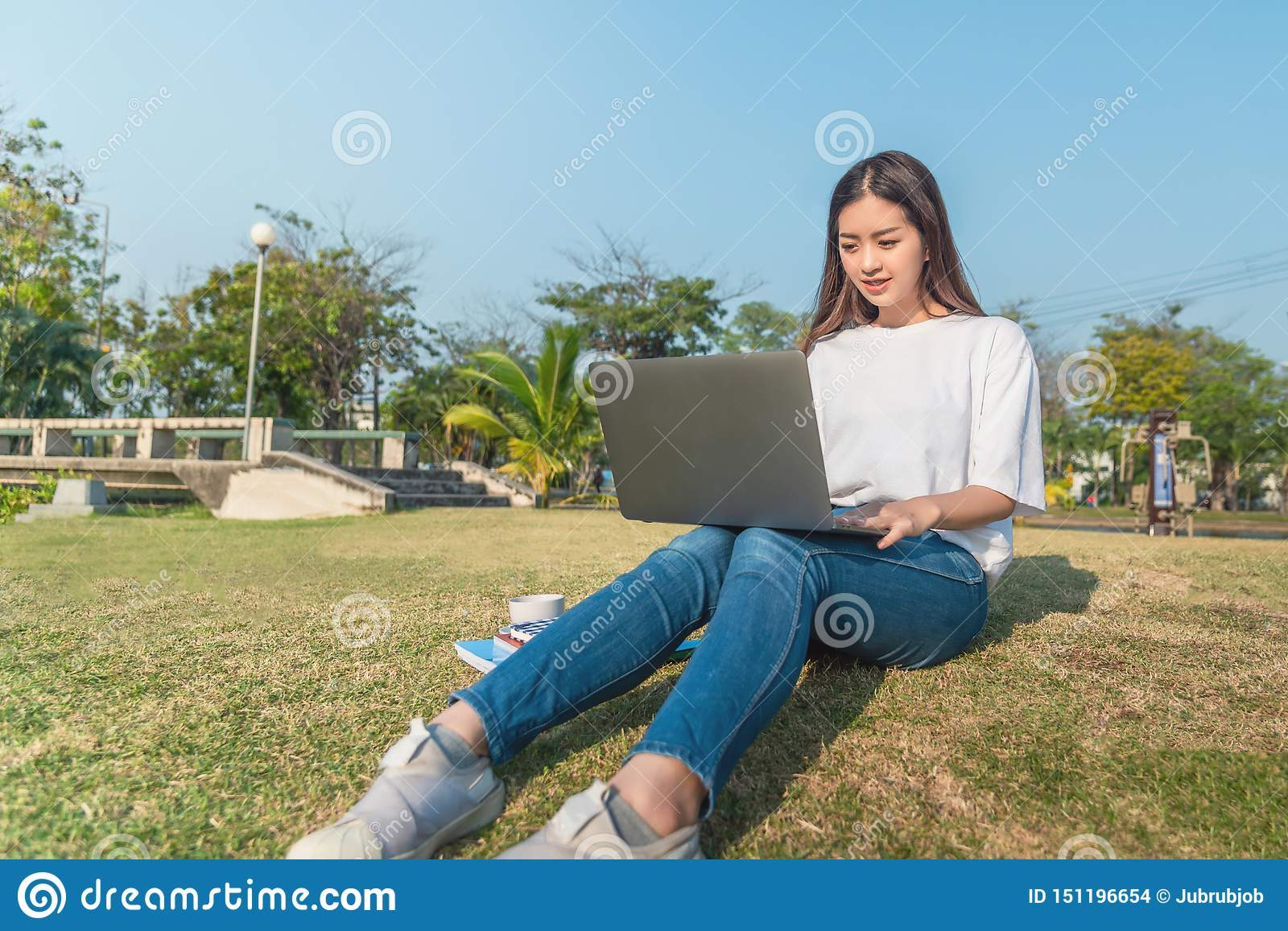 Beautiful young smiling woman using tablet in public park