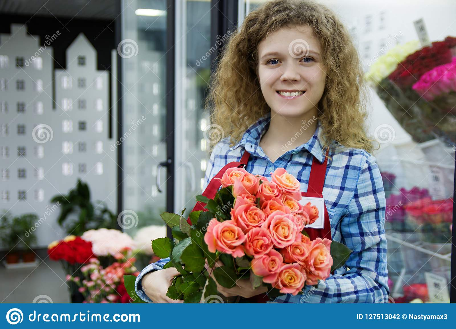 Beautiful young smilling woman florist are selling the bouqet of the roses in flower shop