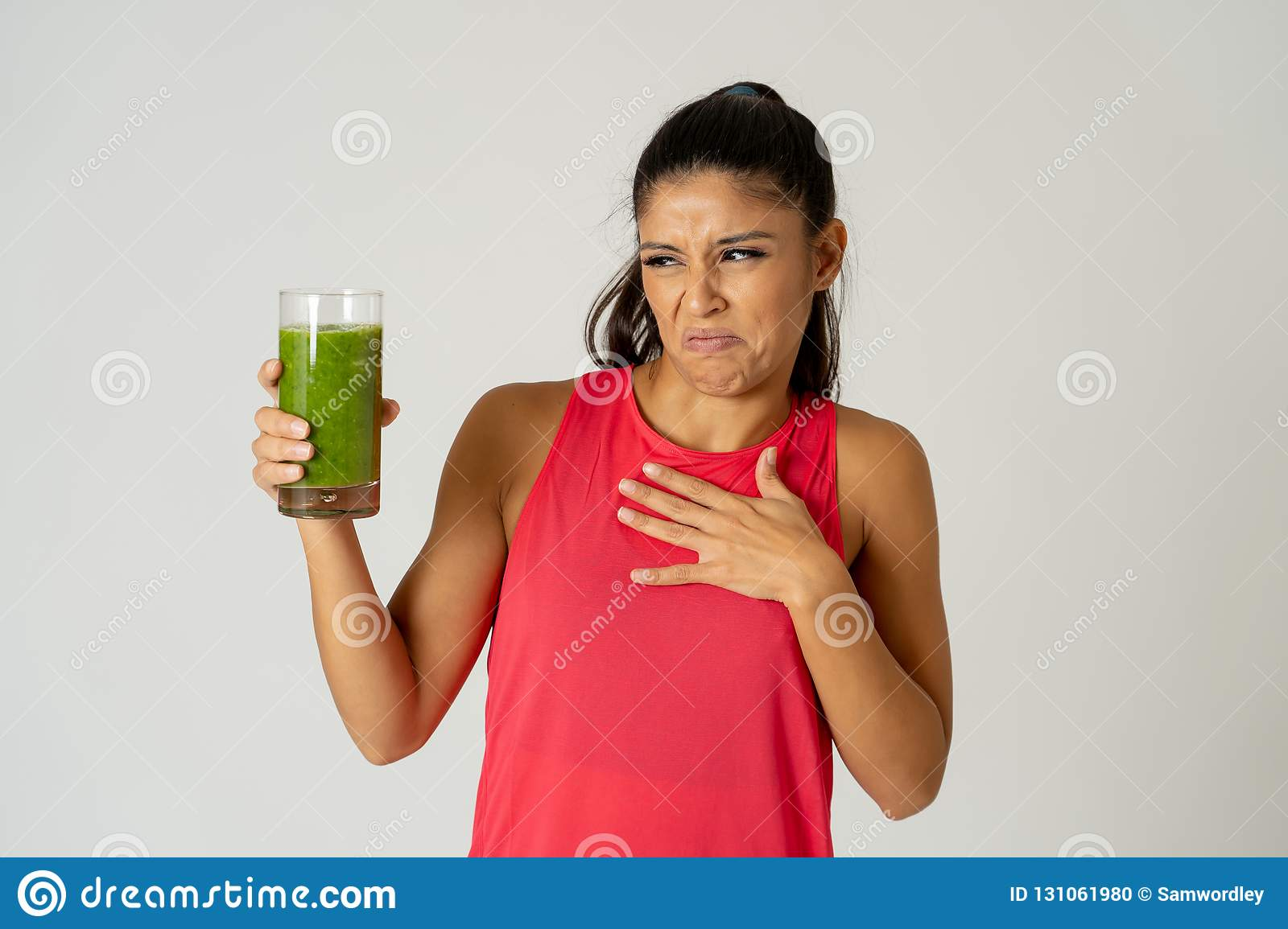 Beautiful young sport woman tired of diet holding green smoothie in dislike