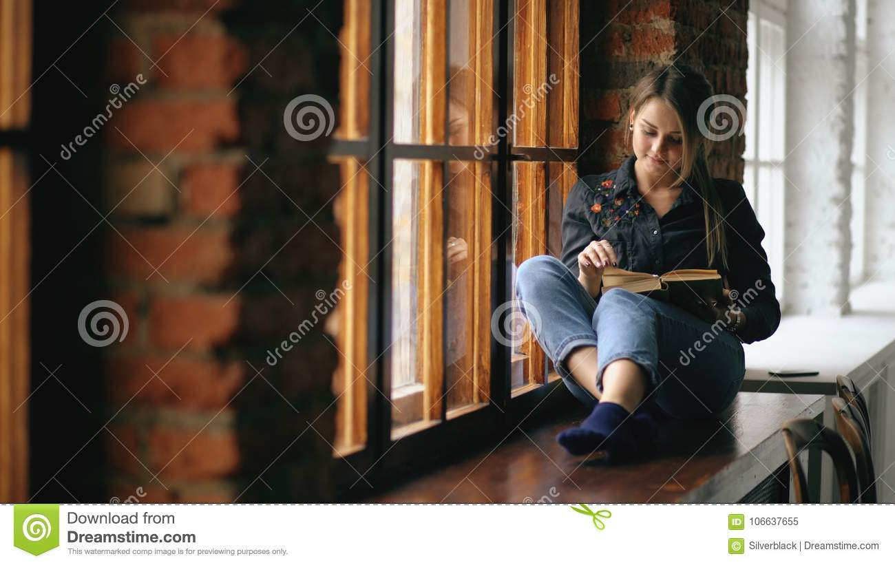 Beautiful young student girl reading book sit on windowsill in university classroom indoors