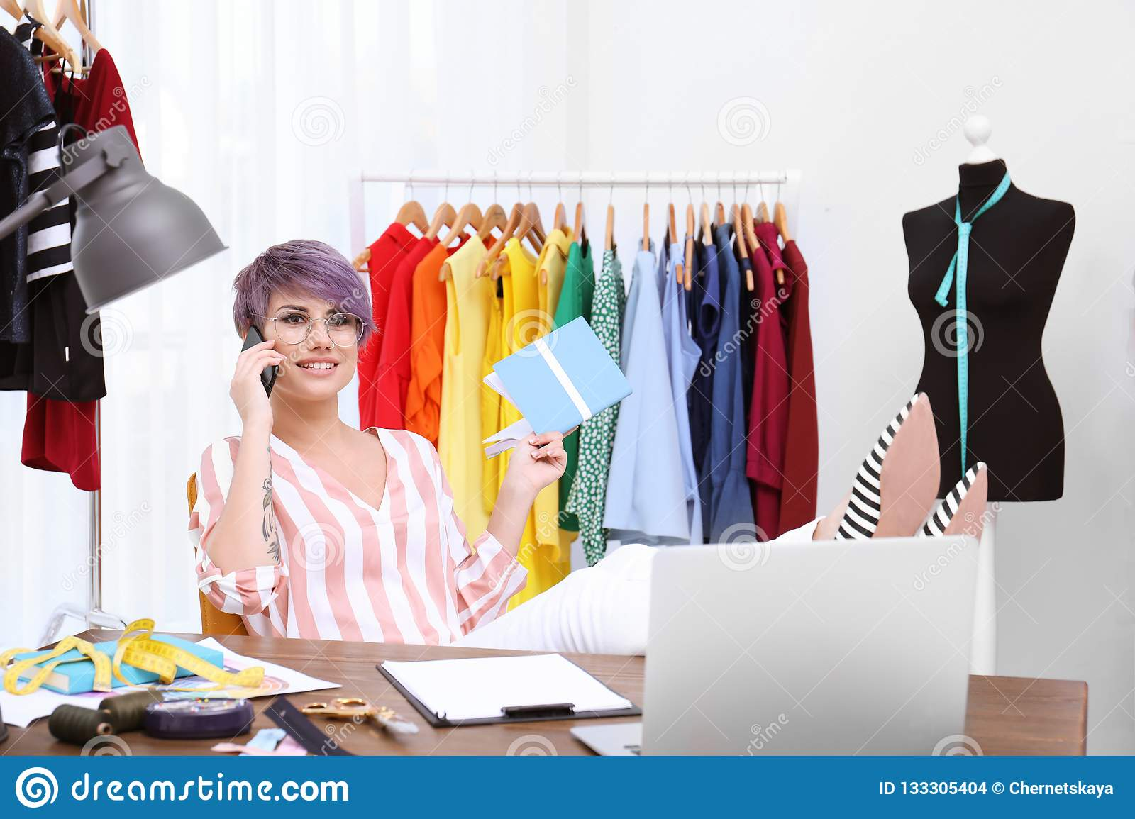 Beautiful young stylist talking on phone at workplace near rack