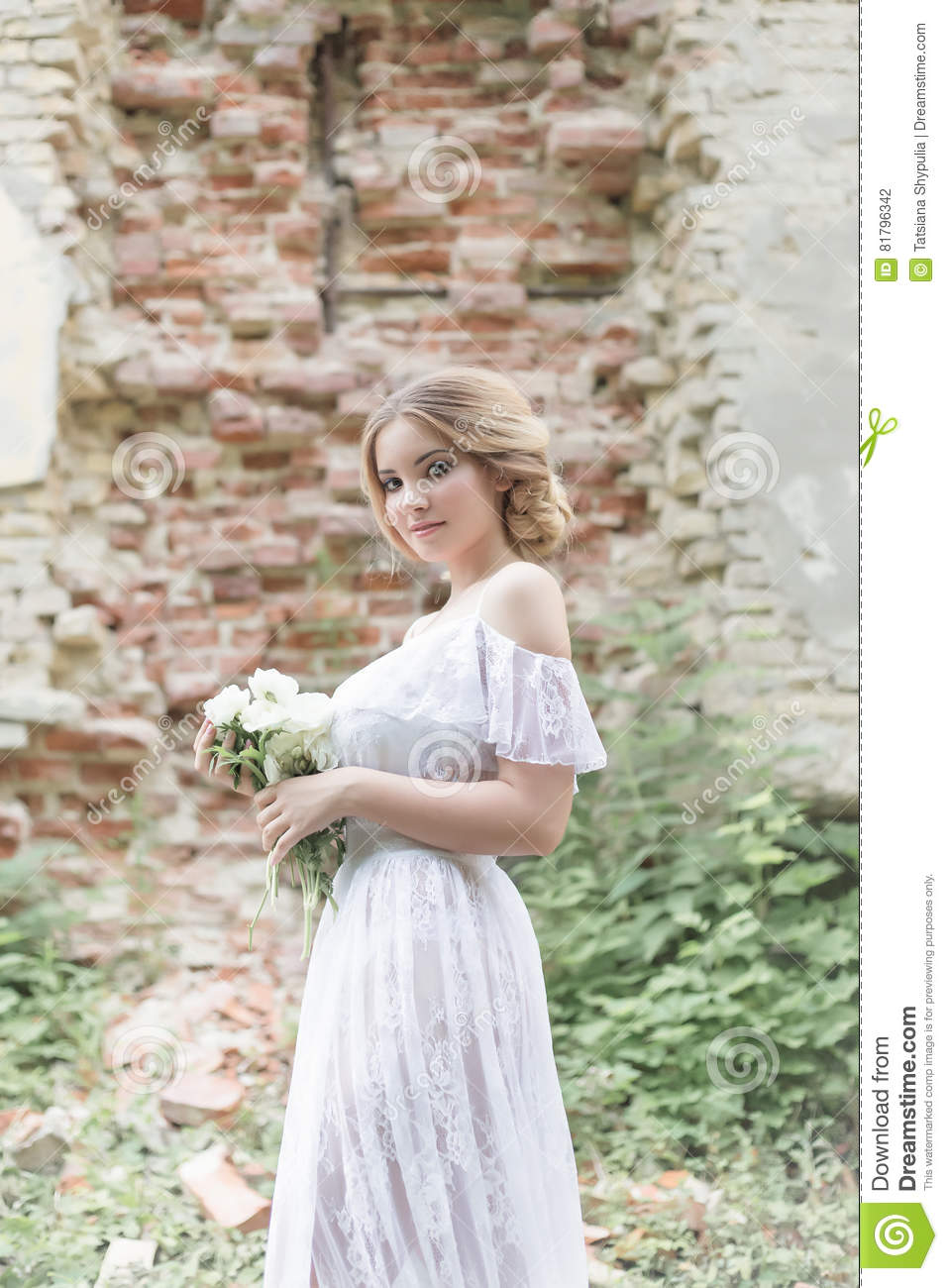 Beautiful young sweet blonde girl with wedding bouquet in the hands of the boudoir in a white dress with evening hairstyle walks