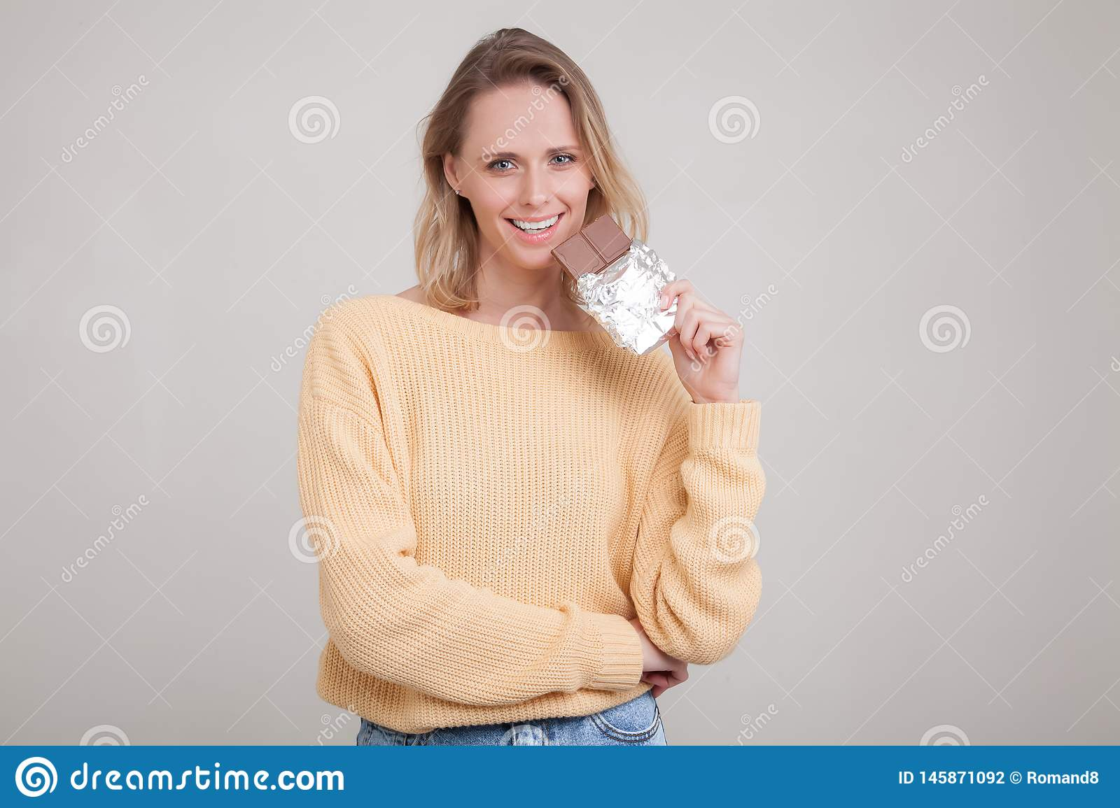 A beautiful young tender girl with blond hair holds a chocolate bar in the face she is wearing in a yellow sweater. poses against