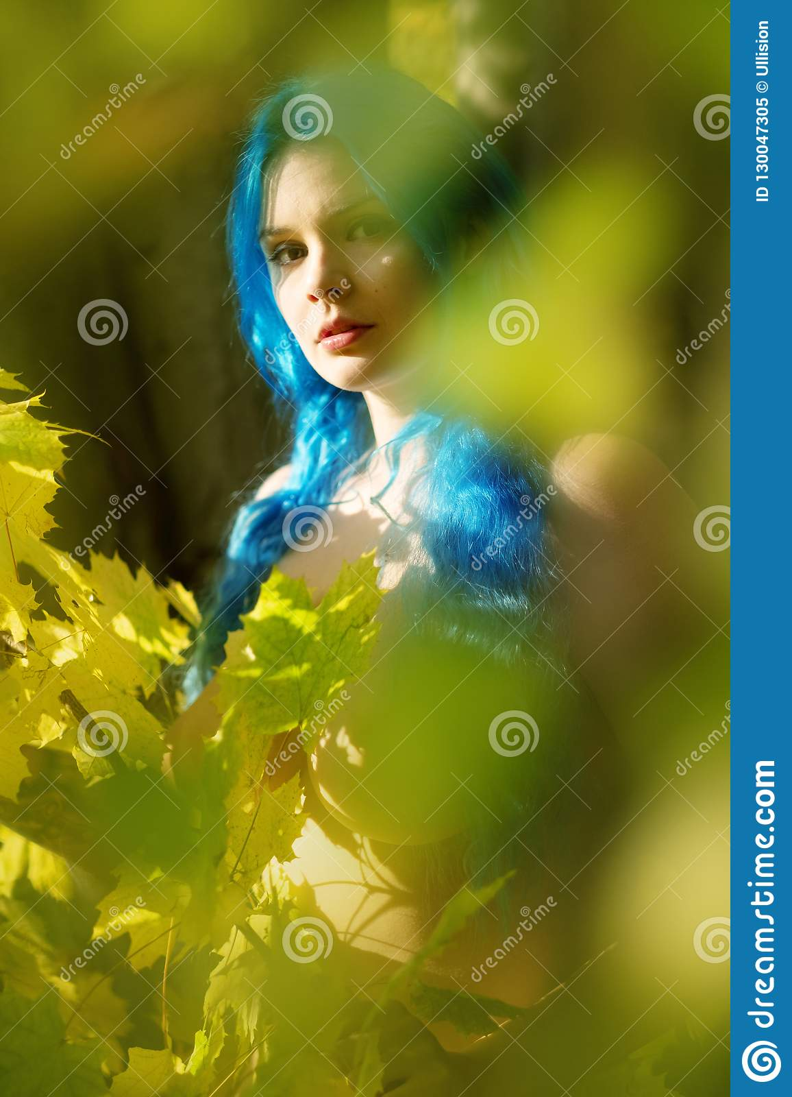 Beautiful young unconventional woman Emo with individual blue hairs, peers out in autumn forest between green yellow leaves.