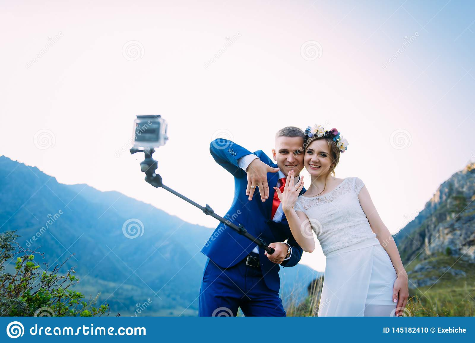 Beautiful young wedding couple making selfie on the background of mountains