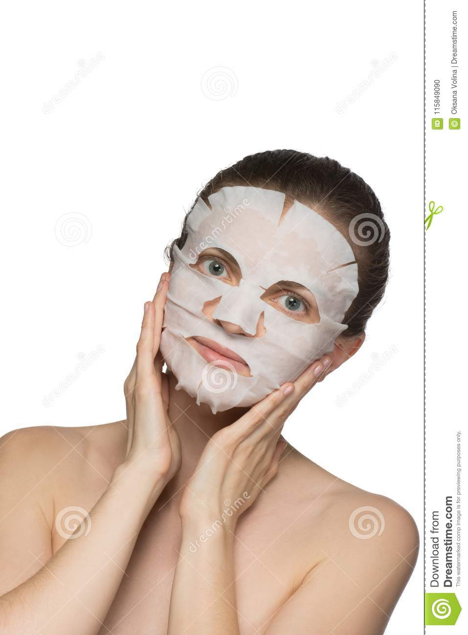 Beautiful young woman is applying a cosmetic mask on a face on a