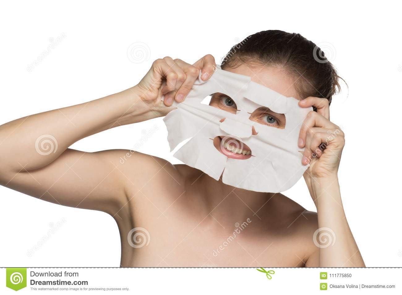 Beautiful young woman is applying a cosmetic mask and smiling on