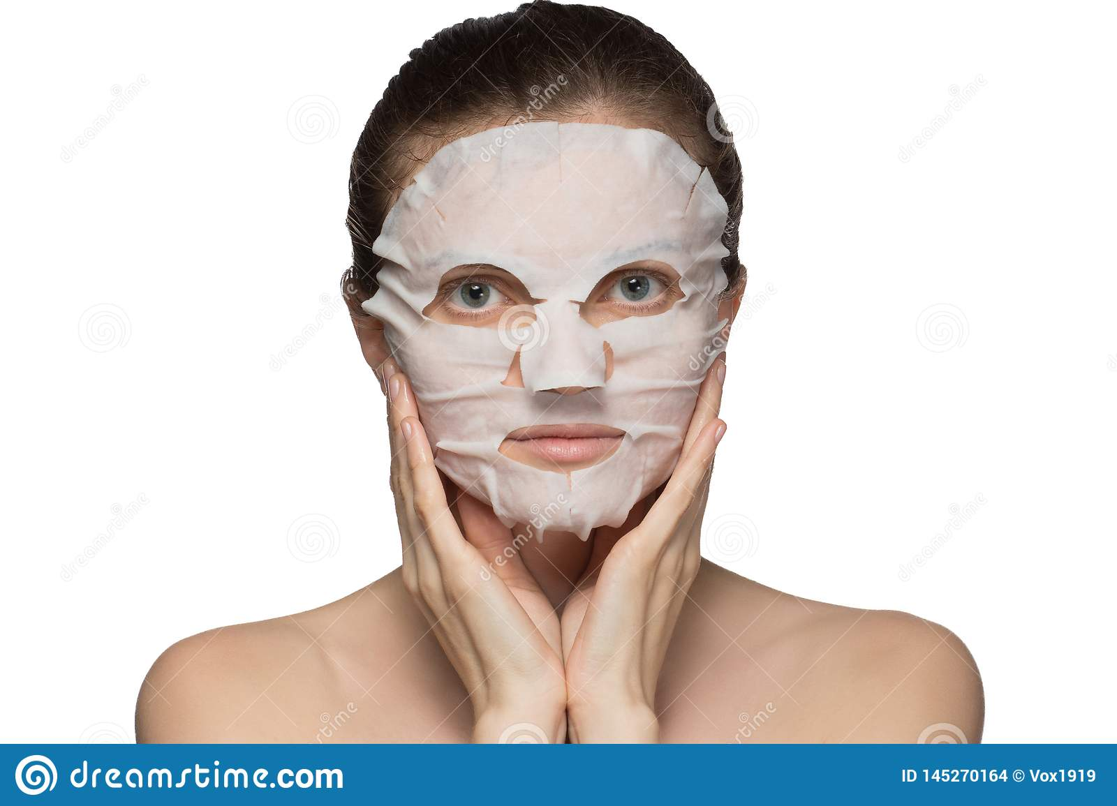 Beautiful young woman is applying a cosmetic mask on a face on a white background