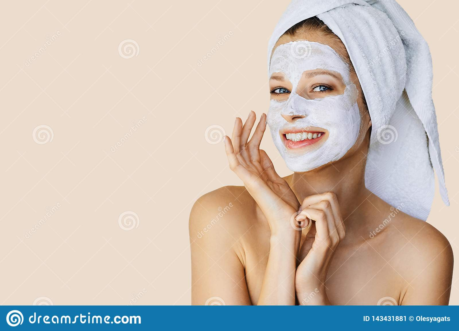 Beautiful young woman applying facial mask on her face. Skin care and treatment, spa, natural beauty and cosmetology concept