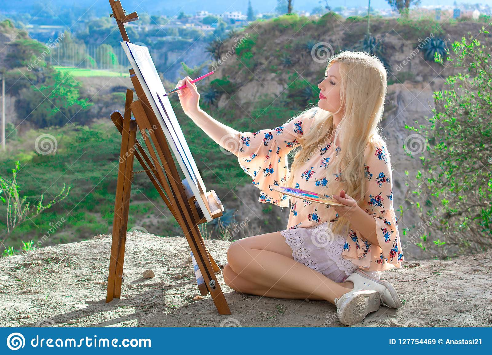 Beautiful young woman artist paints a landscape in nature. Drawing on the easel with colorful paints in the open air.