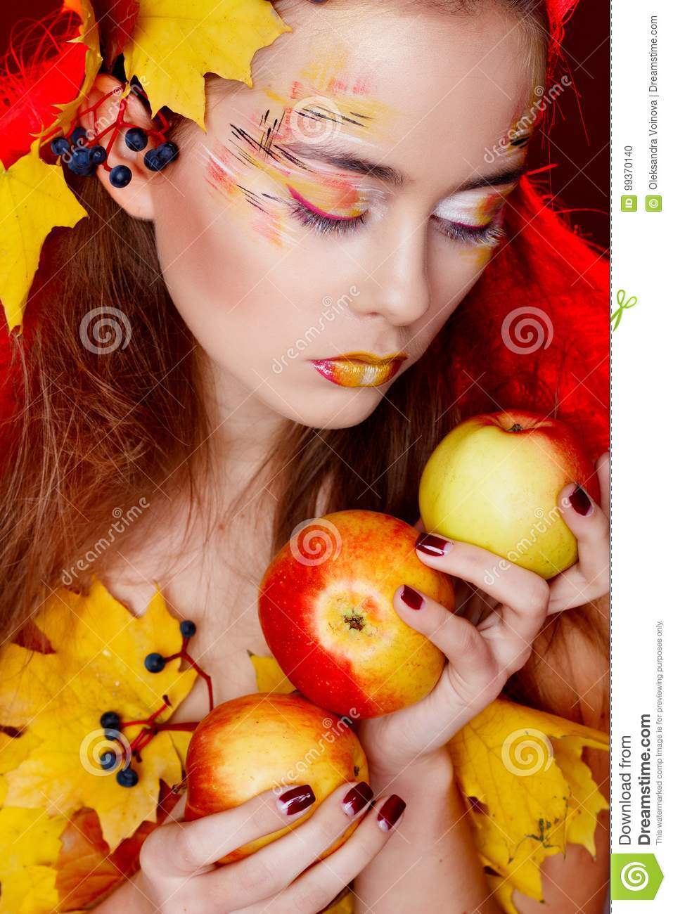 Beautiful young woman with autumn make up holding apples in her