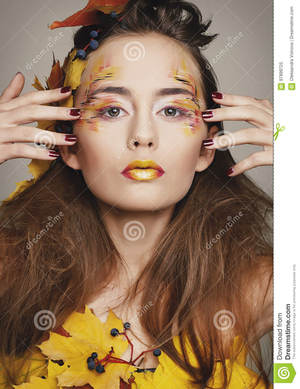 Beautiful young woman with autumn make up posing in studio over