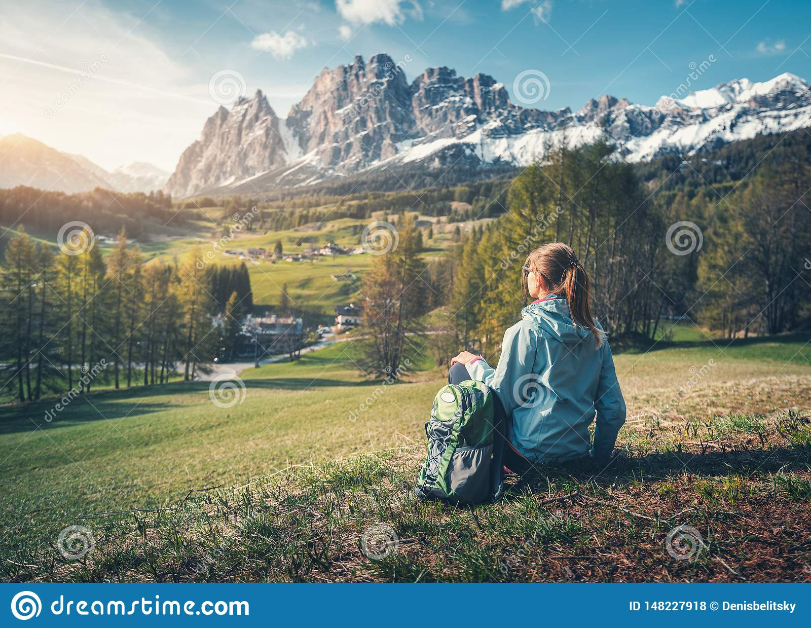 Beautiful young woman with backpack is sitting on the hill