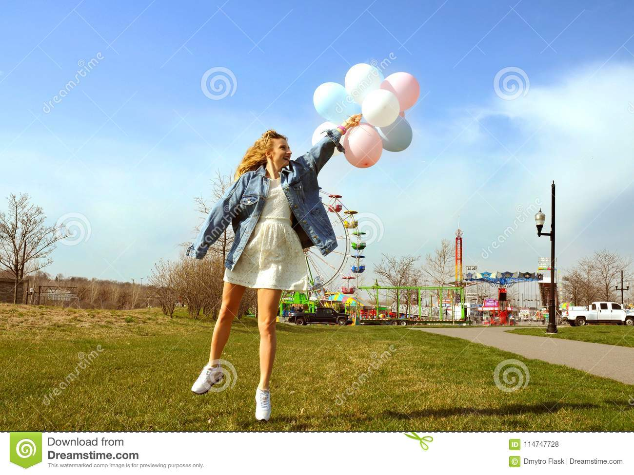 Beautiful young woman with balloons in the amusement park