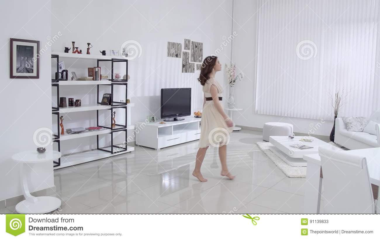 Beautiful Young Woman With Bare Feet And A Beige Dress Moves In The Interior