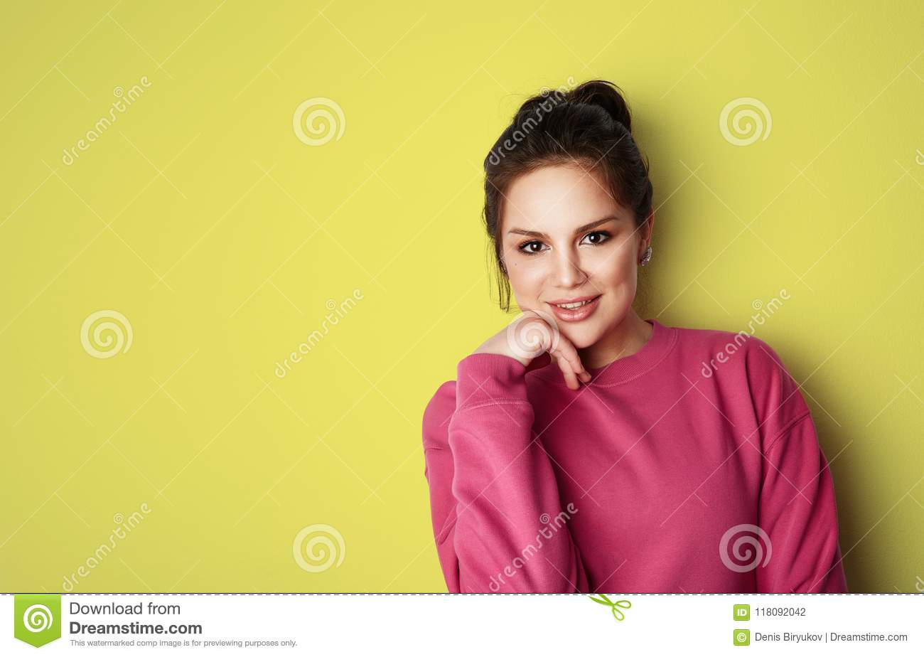 Beautiful young women with big brown eyes wearing pink hoody and looking at camera over empty yellow background.Model