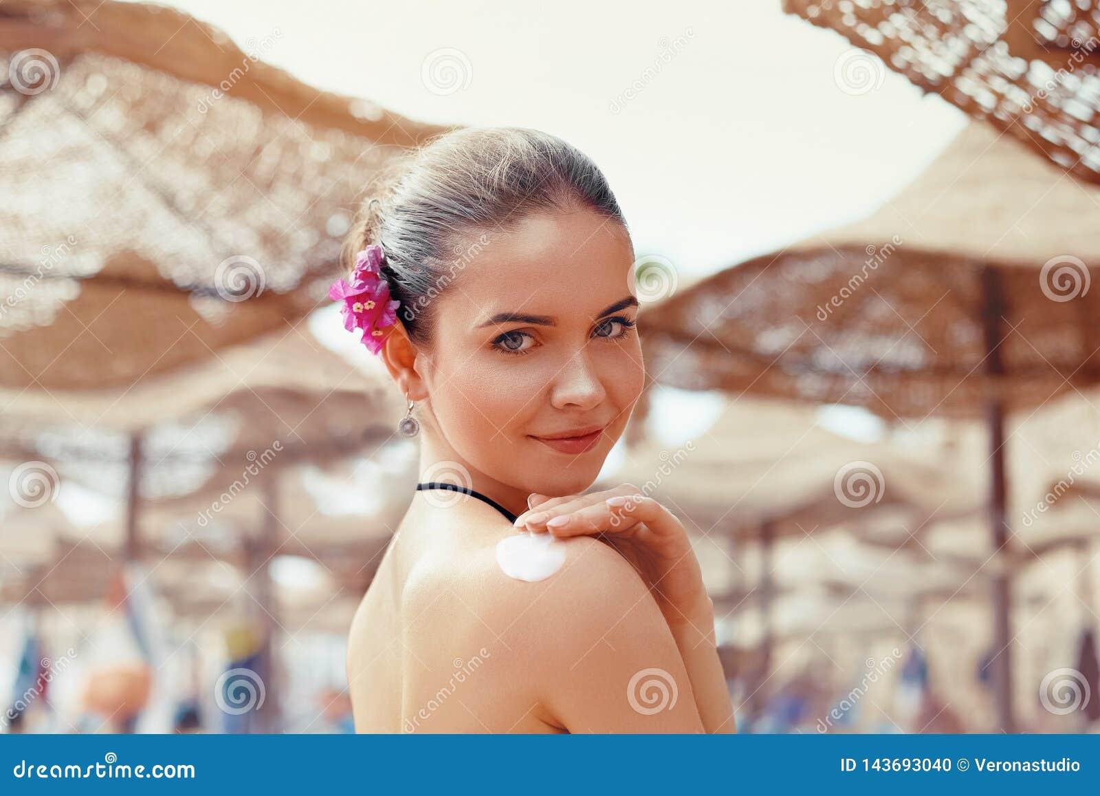 Beautiful young woman in bikini smear protective cream on the skin on the beach under the sun.