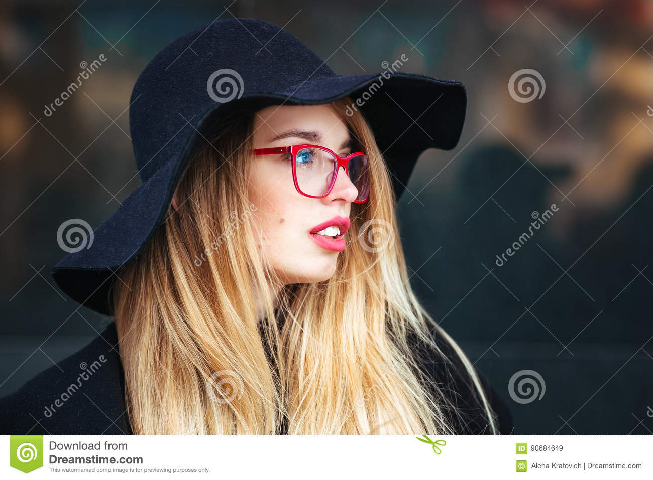 ef4afdd77283 Stock photo beautiful young woman black coat hat wearing red glasses red  bag walking city reflection