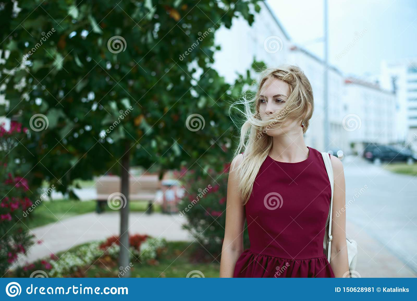 Beautiful young woman blonde with long hair in a fashionable burgundy dress