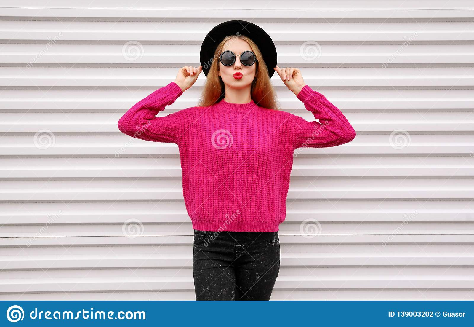 Beautiful young woman blowing red lips sending sweet air kiss in colorful pink knitted sweater