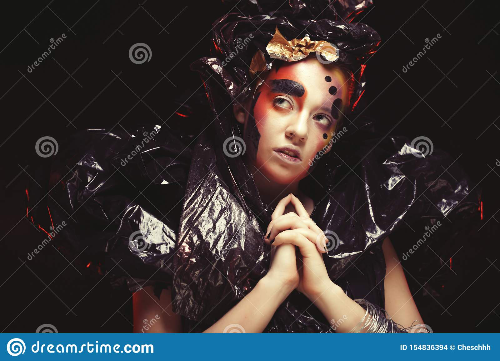 Beautiful young woman with bright fantasy make-up and costume posing on a black background in clouds of smoke. Halloween