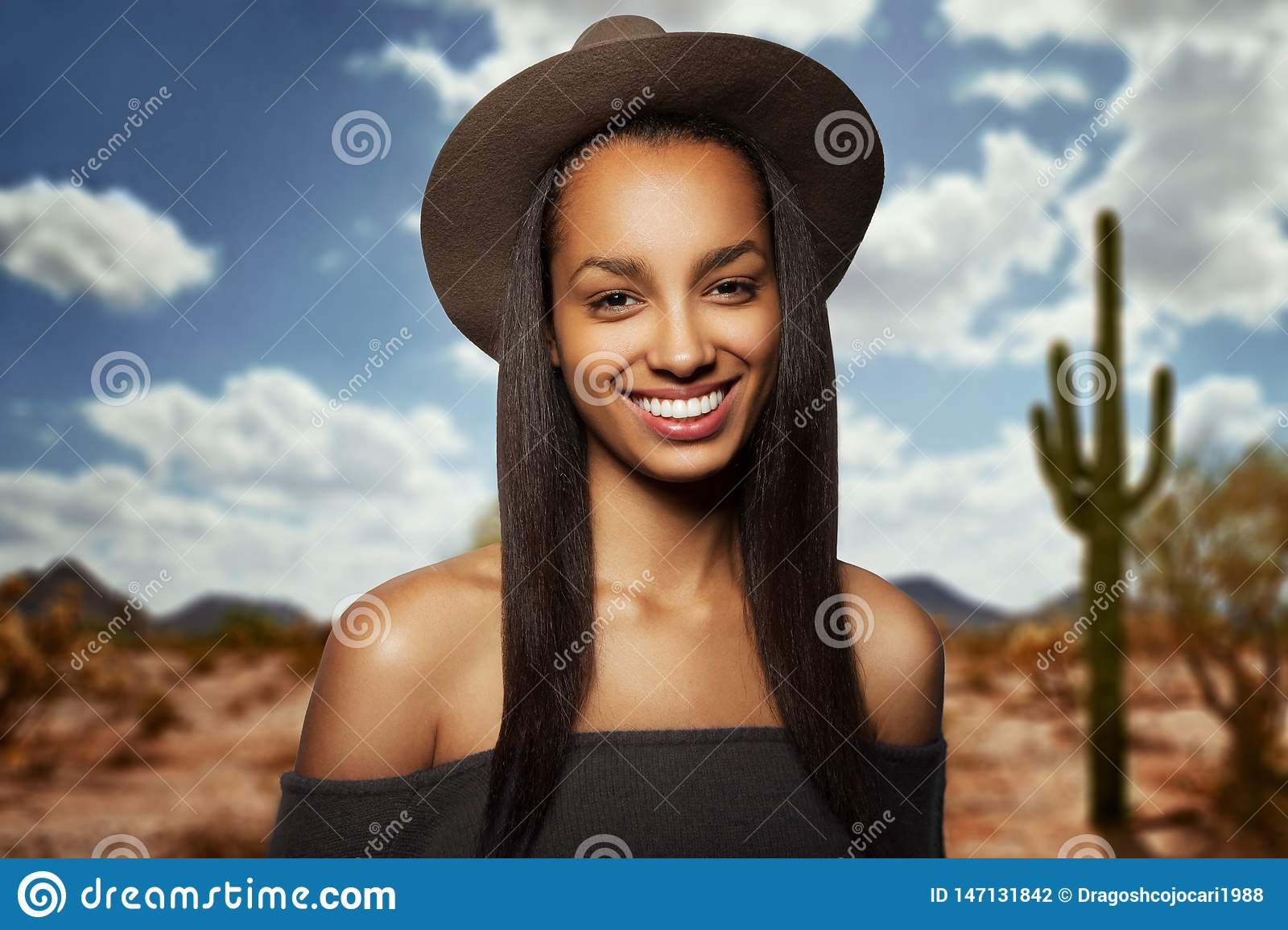 Beautiful young woman with brown hat, long hair, smiling, with naked shoulders, isolated on a blurry desert background.