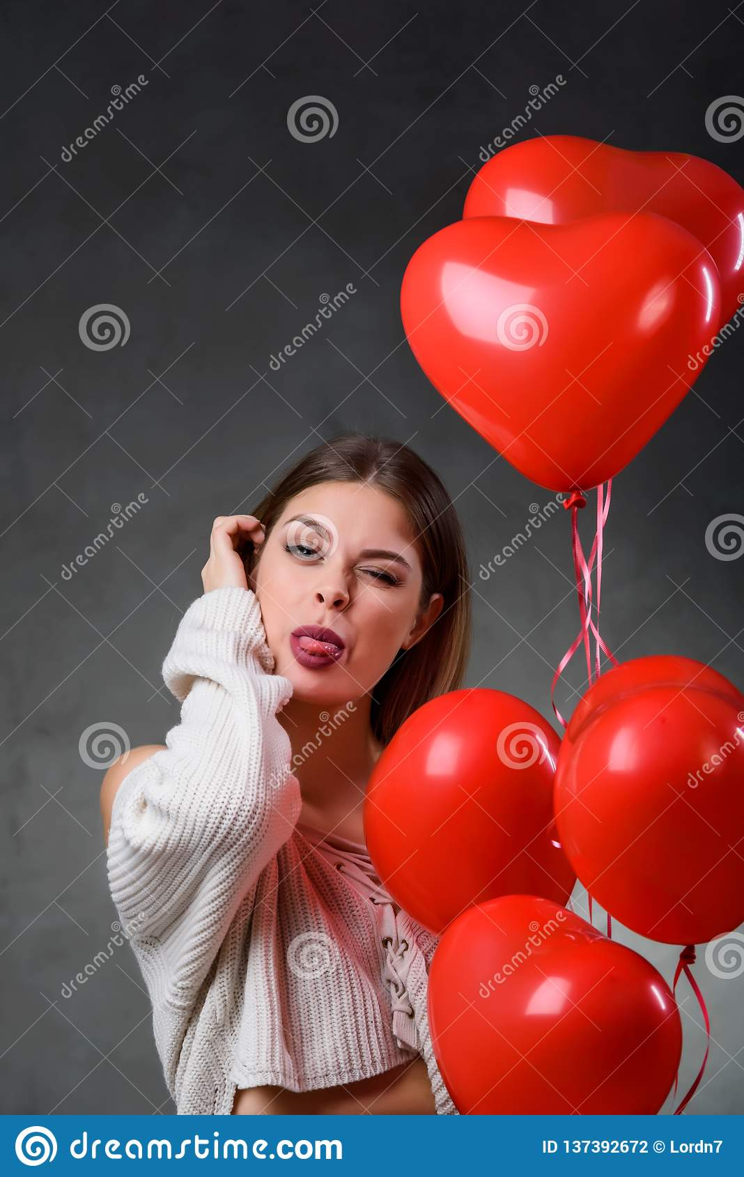 Beautiful young woman with bunch of red heart balloons