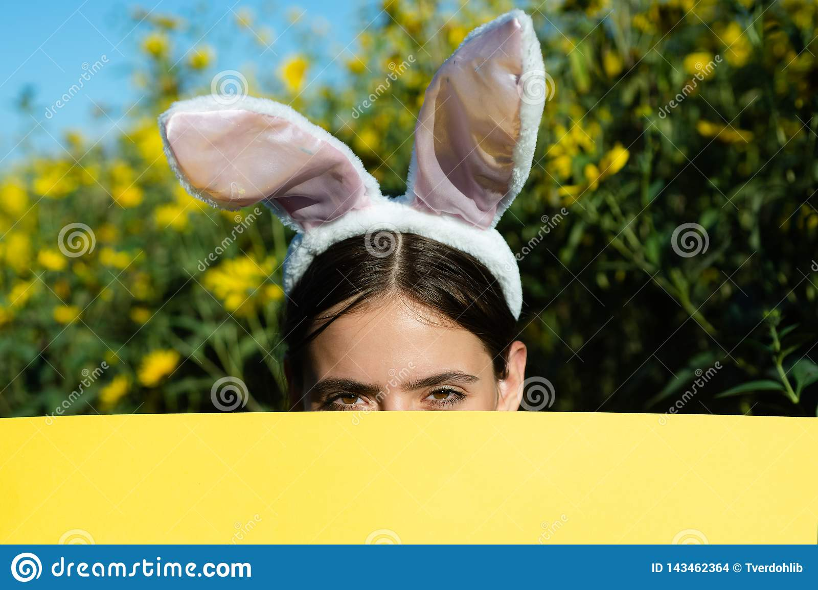 Beautiful young woman with bunny ears and blank poster on outdoor background. Copy space. Easter holiday concept