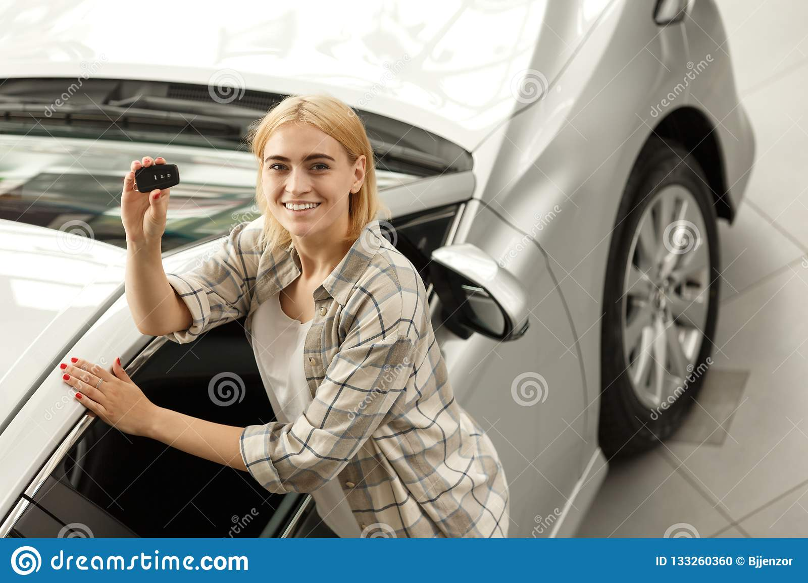 Beautiful young woman buying new car at the dealership