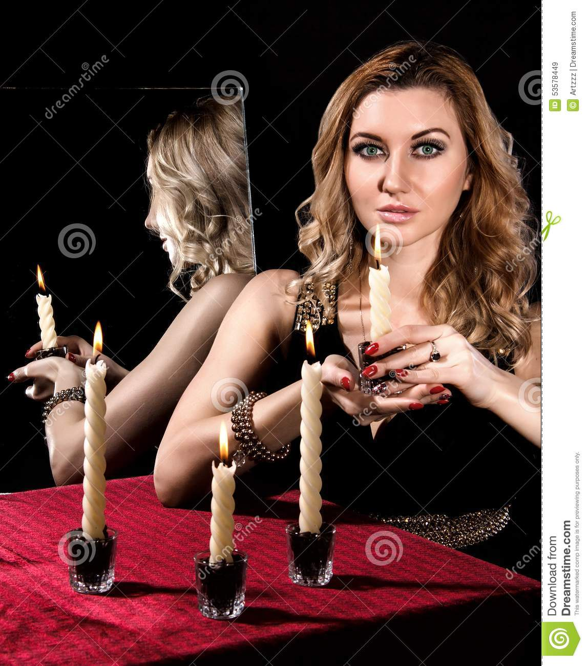 Beautiful young woman with candles near the mirror