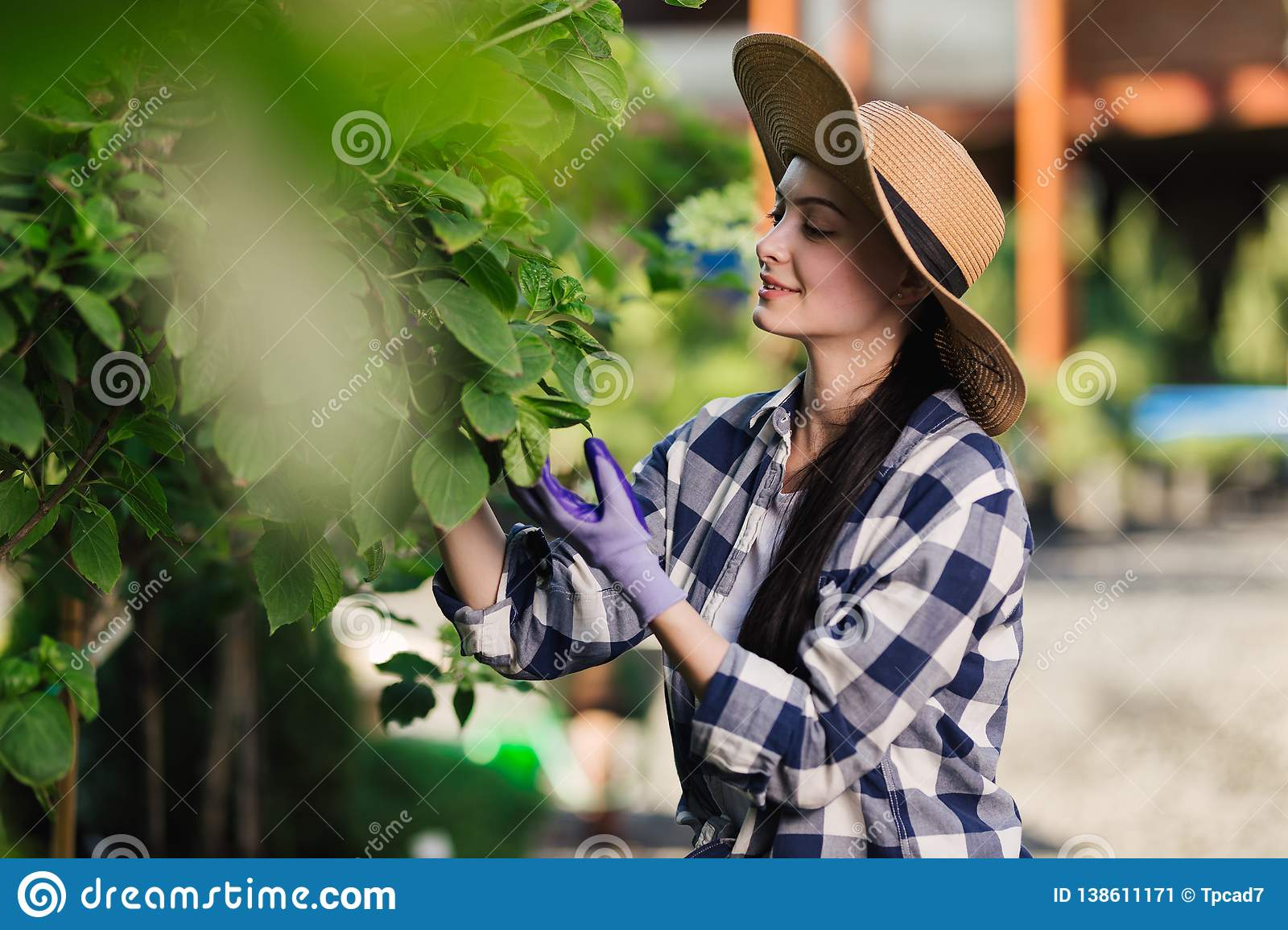 Beautiful young woman in checkered shirt and straw hat gardening outside at summer day