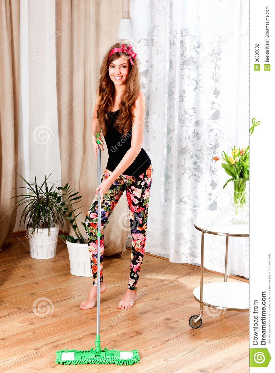 Beautiful Young Woman Cleaning Up The Living Room Stock