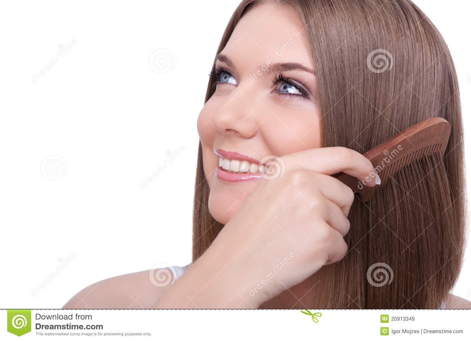 Beautiful young woman combing her hair