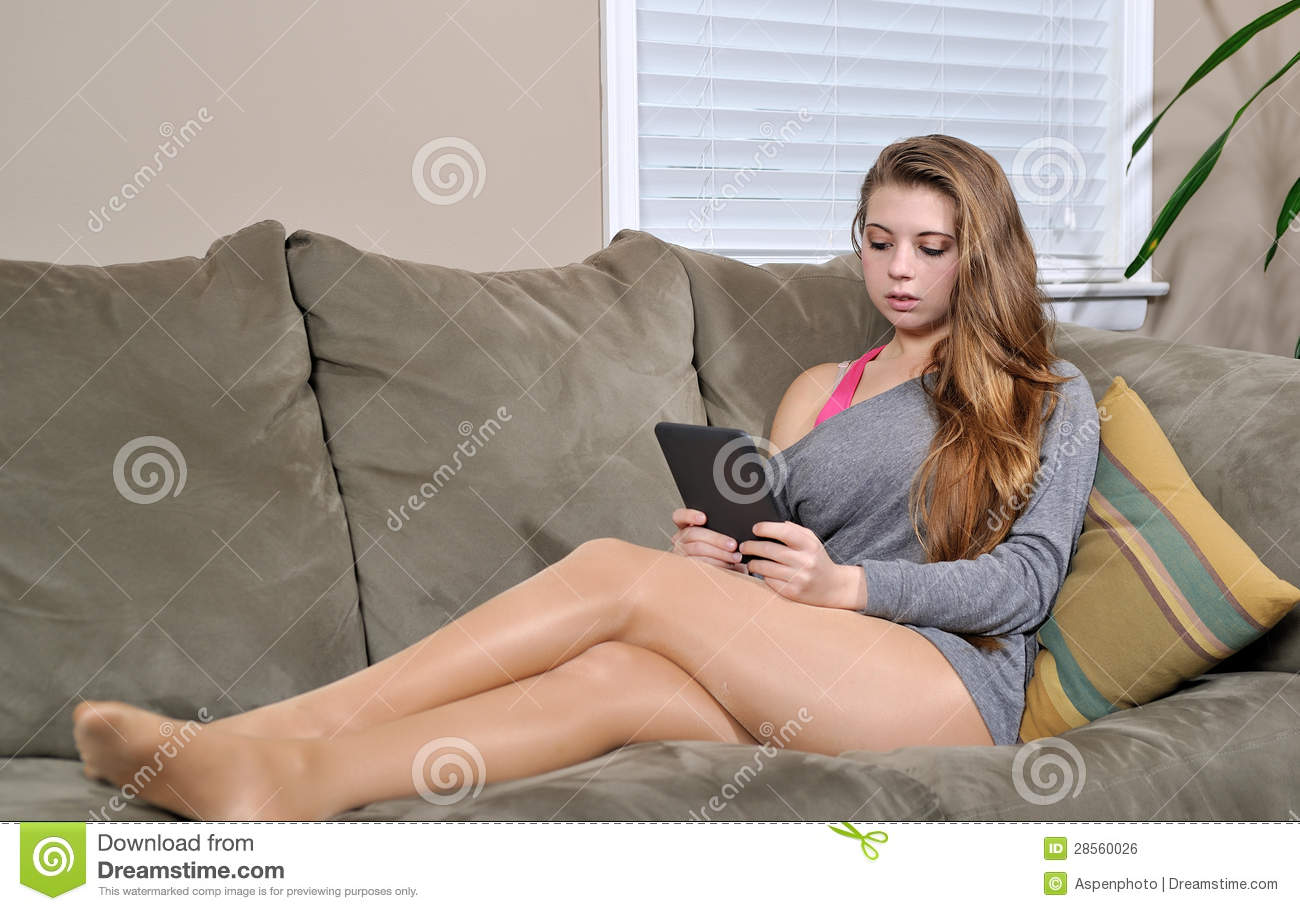 Beautiful Young Woman On Couch With E Reader Royalty Free