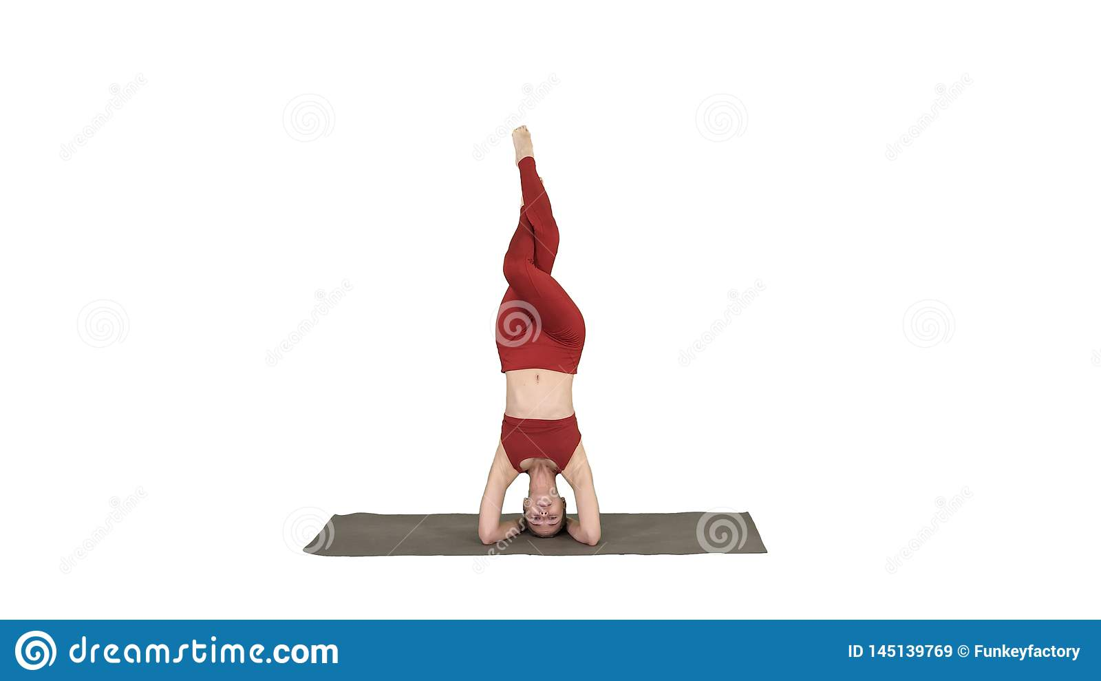 Beautiful young woman doing yoga exercise variation of supported headstand, garuda salamba sirsasana with crossed legs
