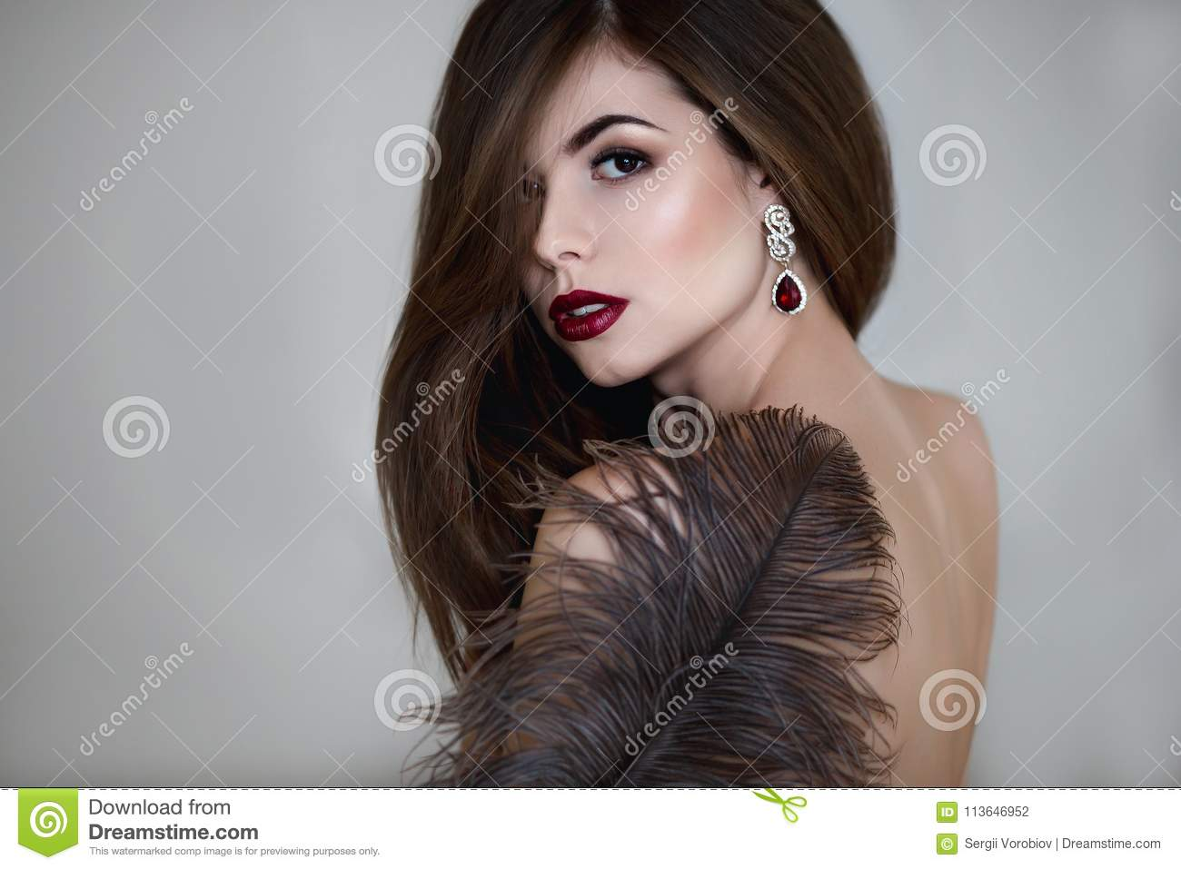 Beautiful young woman. Dramatic indoor portrait of sensual brunette female with long hair. Sad and serious girl.