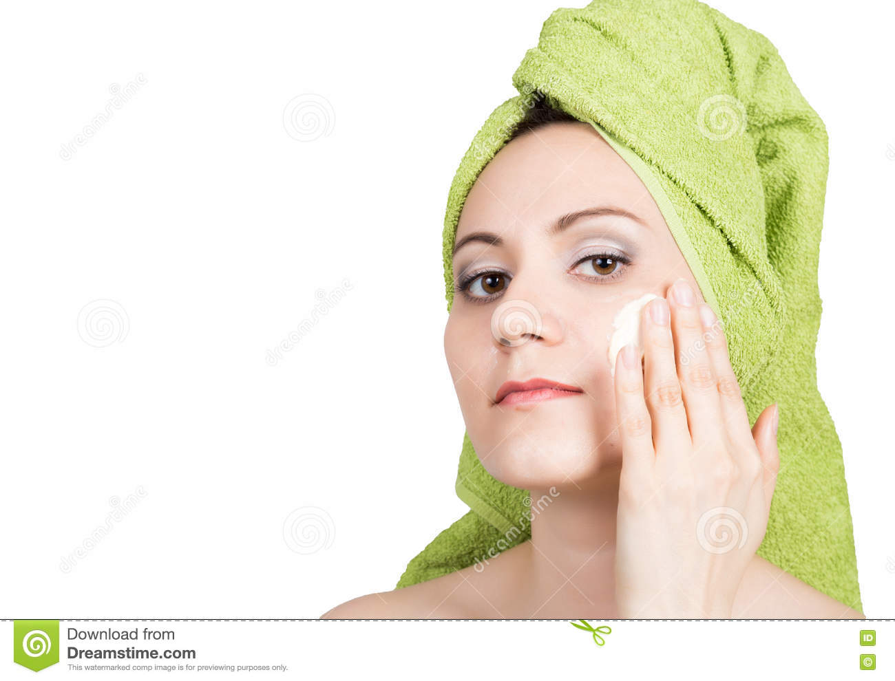 Beautiful Young woman dressed in a bath towel makes cosmetic mask on the face. beauty industry and home skin care