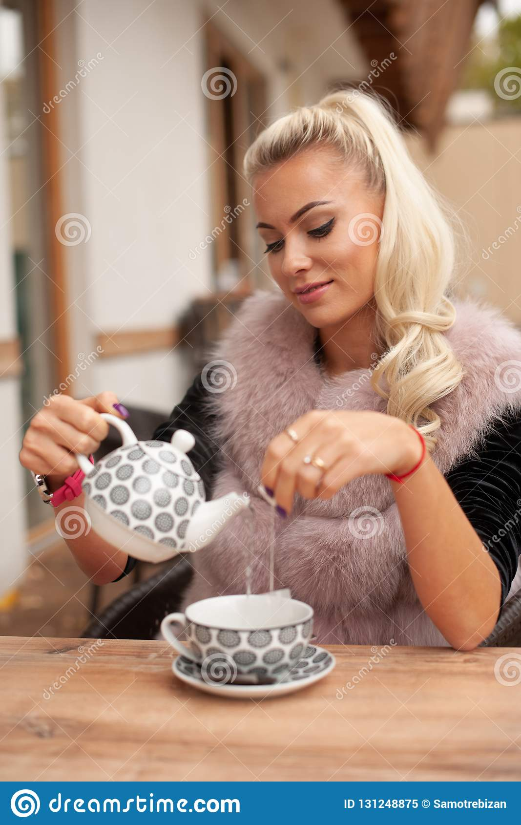 Beautiful young woman drink tea on bar terace in early autumn