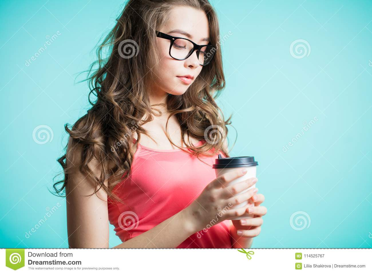 Beautiful young woman drinking coffee. Young brunette woman holding a paper Cup on her hand on a blue background
