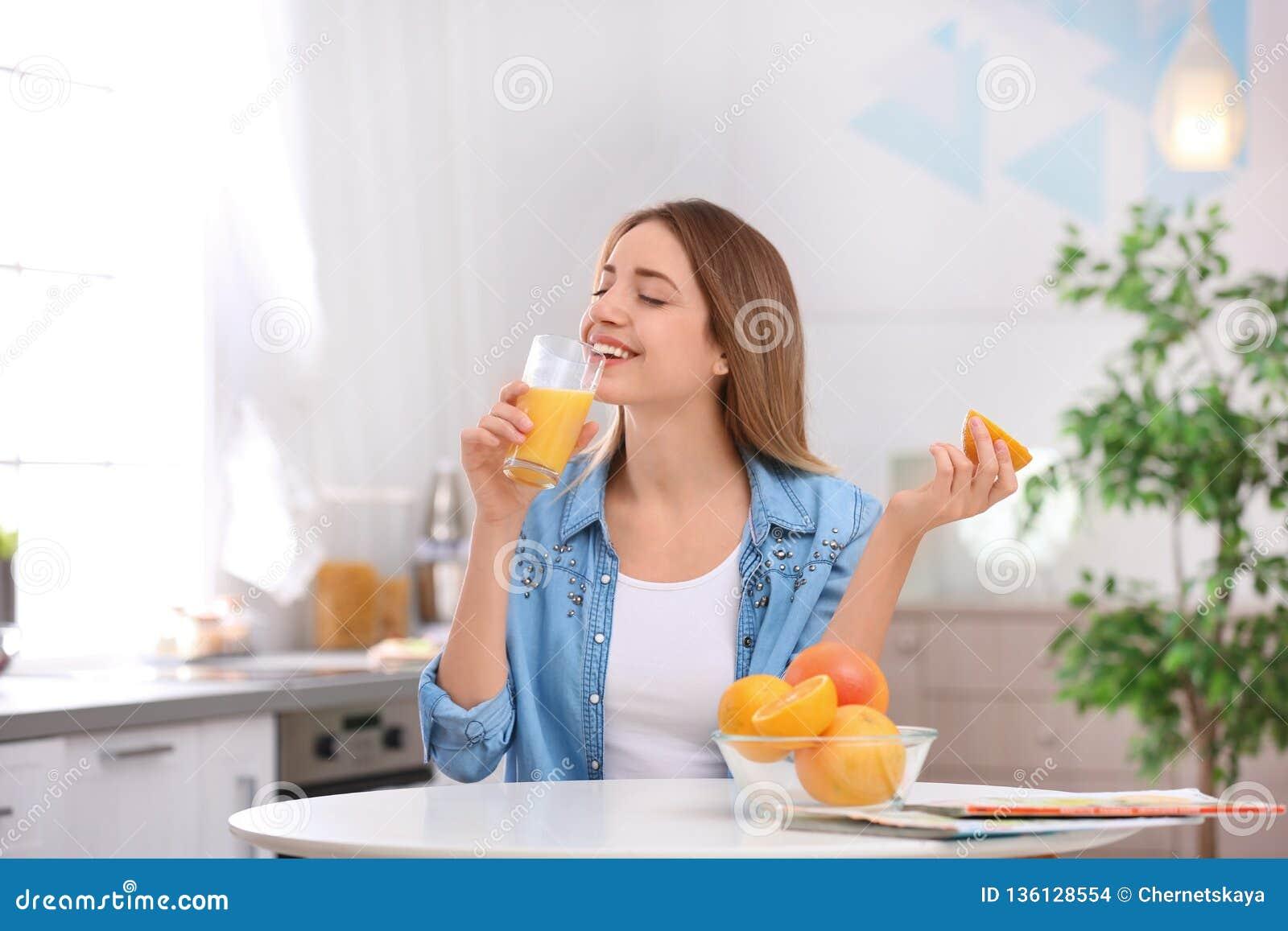 Beautiful young woman drinking fresh orange juice in kitchen