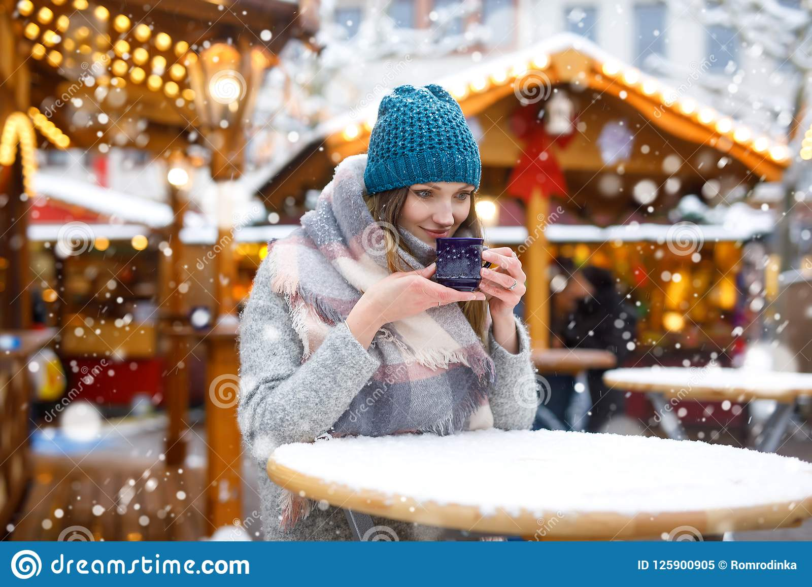 Beautiful young woman drinking hot punch, mulled wine on German Christmas market. Happy girl in winter clothes with