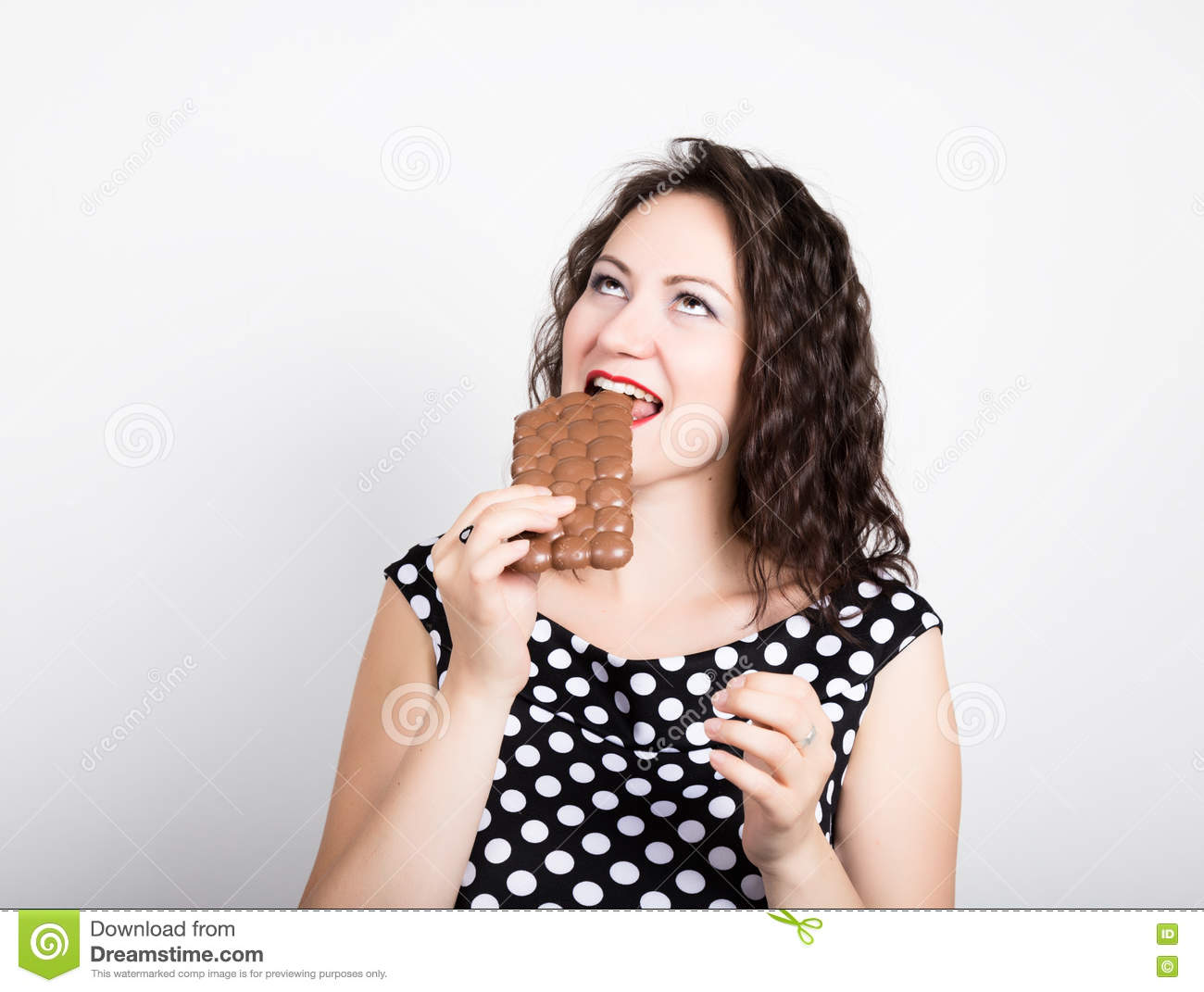 Beautiful Young Woman Eating A Chocolate Bar Wears A Dress With
