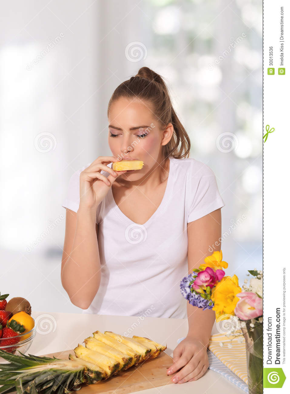 beautiful young woman eating pineapple stock photo