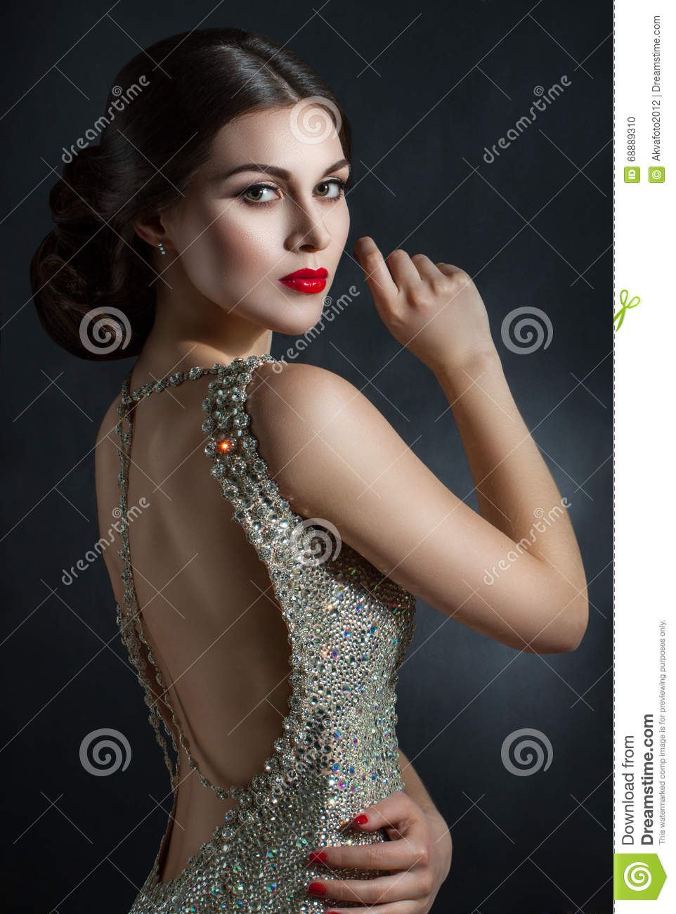 Beautiful young woman in an evening dress crystal. Perfect beauty, red lips, bright makeup. Twinkling sparkling stones on dress
