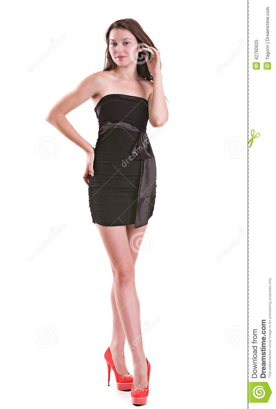 99c41552cfb Young beautiful girl in a black short evening dress with a belt in the form  of a bow on a white background