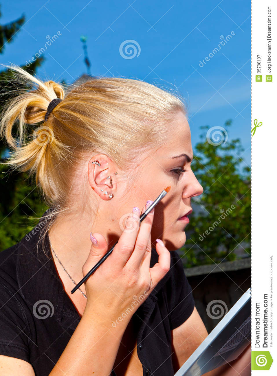 Beautiful young woman face with applying beauty make-up