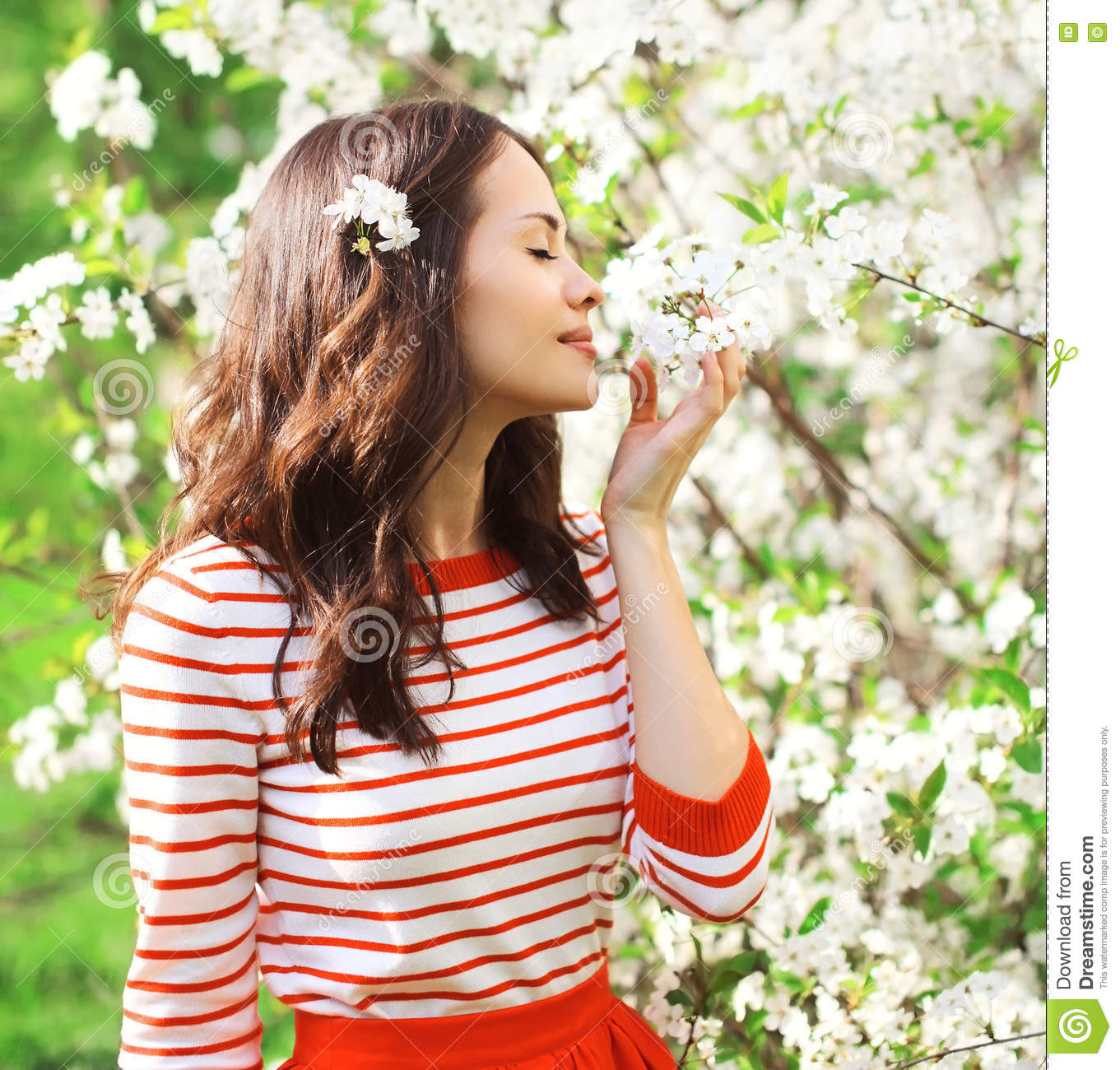 Beautiful young woman in a flowering spring garden enjoying petals of flowers