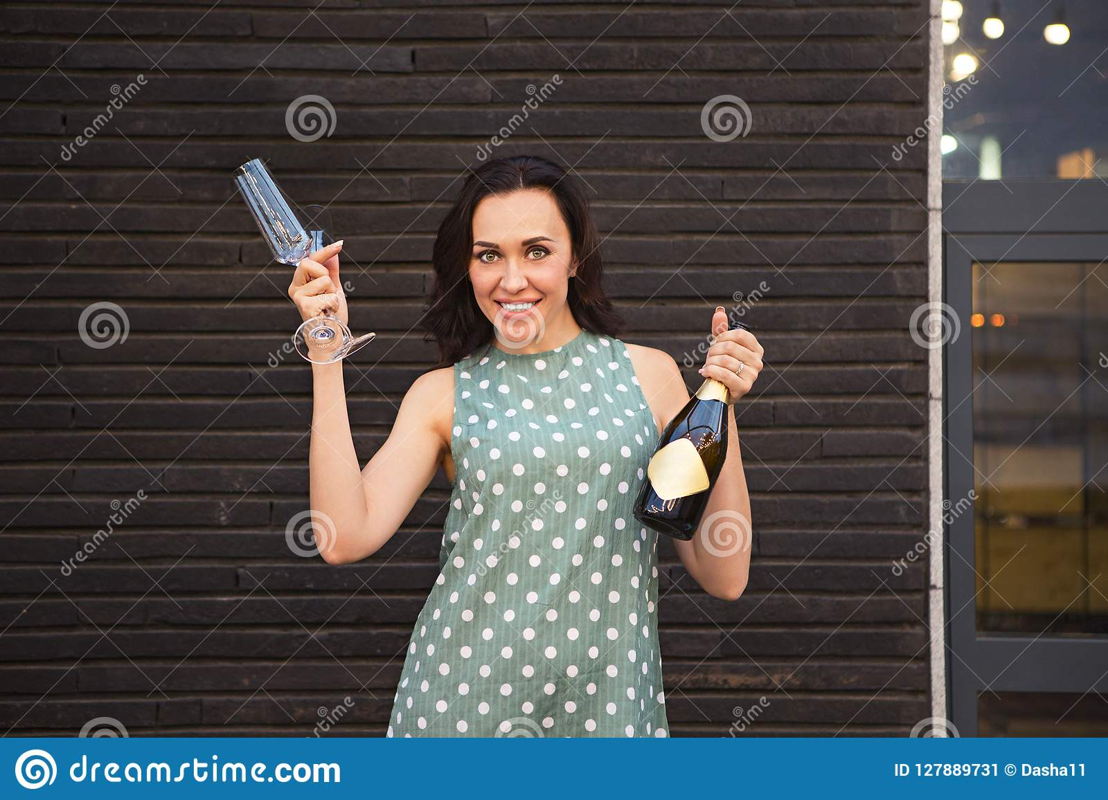 Beautiful young woman in a green polka dots dress holding two glasses and champagne bottle