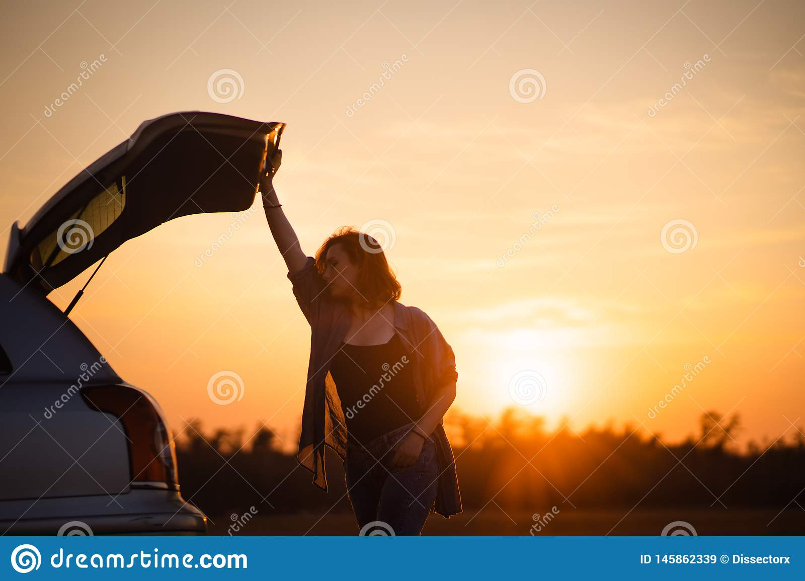 Beautiful young woman happy and dancing in a car`s trunk during a road trip in Europe in the last minutes of Golden Hour